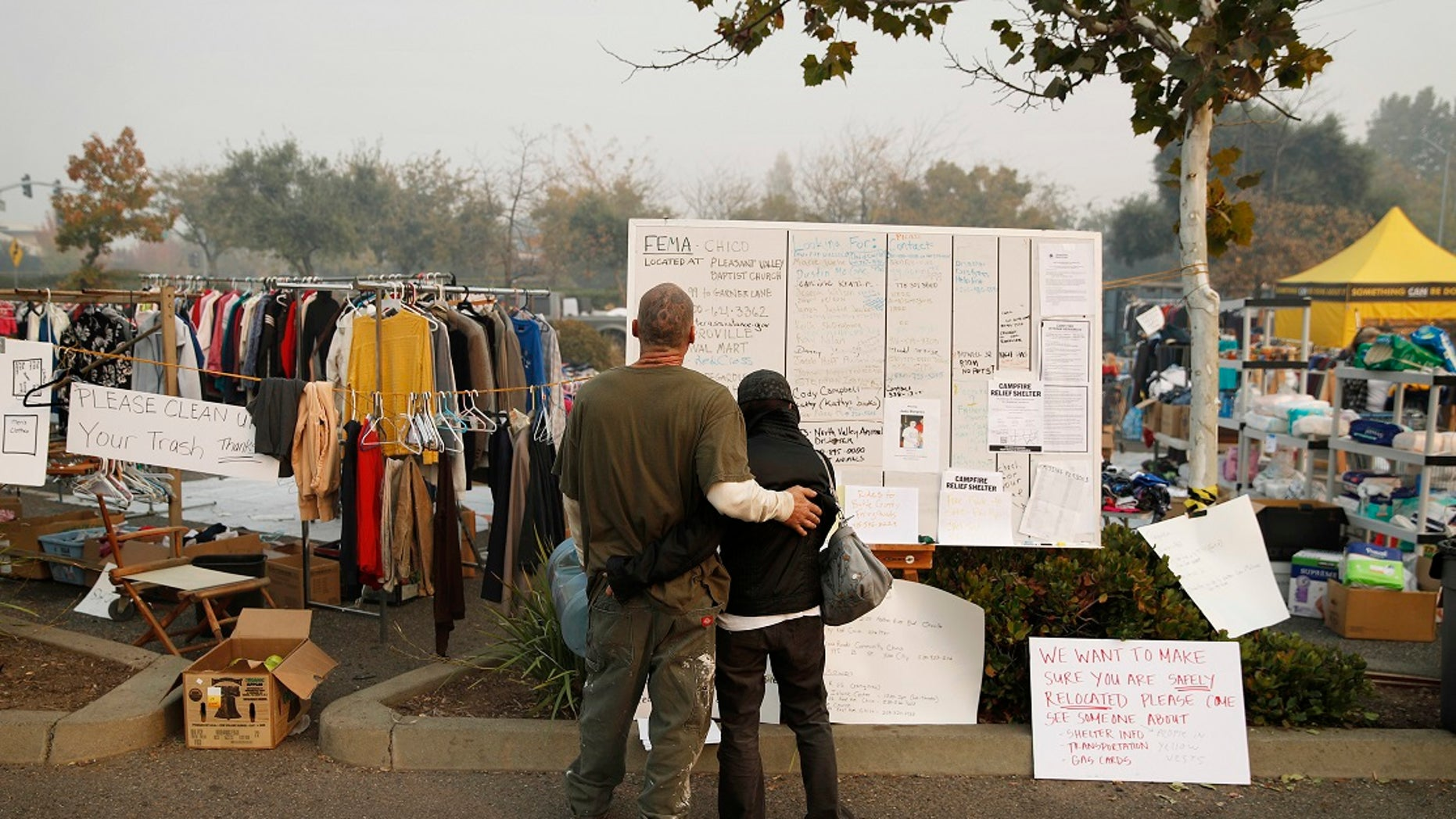 Tera Hickerson, right, and Columbus Holt embrace as they look at a board with information for services at a makeshift encampment outside a Walmart store for people displaced by the Camp Fire.