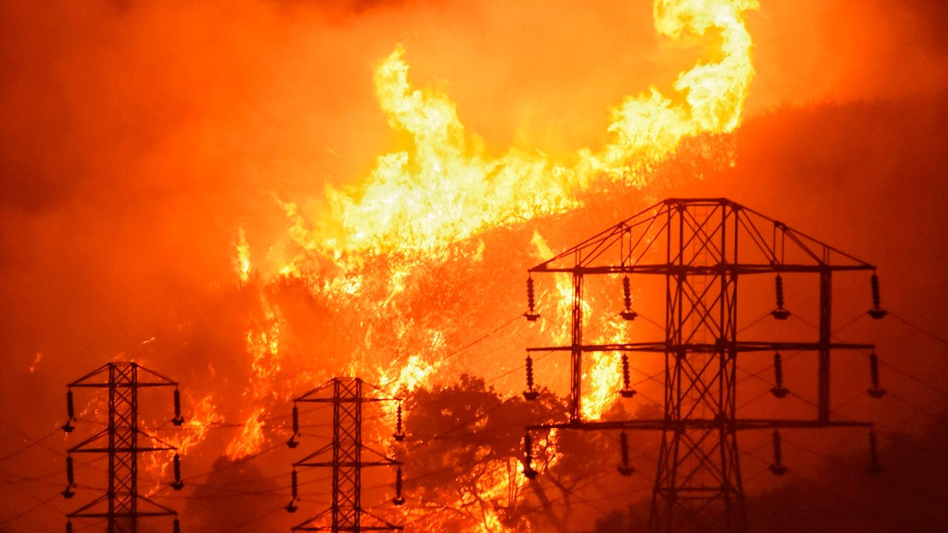 FILE -Flames burn near power lines in Montecito, Calif., Dec. 16, 2017. (Mike Eliason/Santa Barbara County Fire Department via AP)