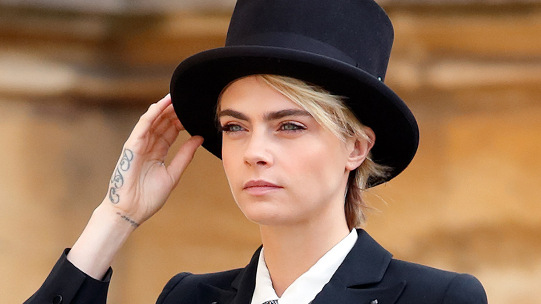 Cara Delevingne attended Princess Eugenie's royal wedding a suit and top hat.
