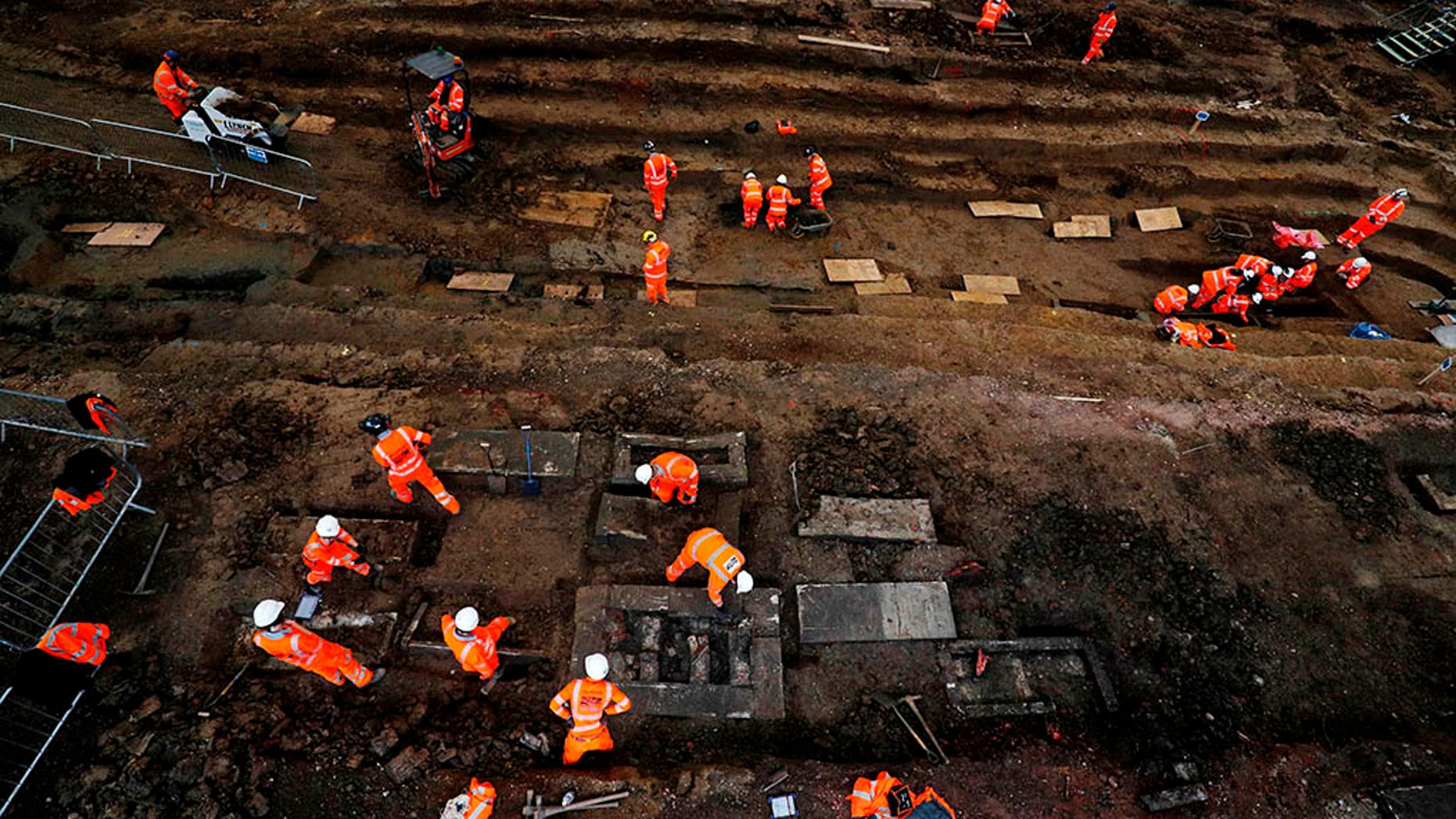 Field archaeologists work on the excavation of a late 18th to mid 19th-century cemetery under St James Gardens near Euston train station in London on November 1, 2018, as part of the HS2 high-speed rail project. - Tucked behind one of London's busiest railway stations, a small army of archaeologists shovel thick clay as they clear a vast burial site to make way for a new train line.  (Photo by Adrian DENNIS / AFP)