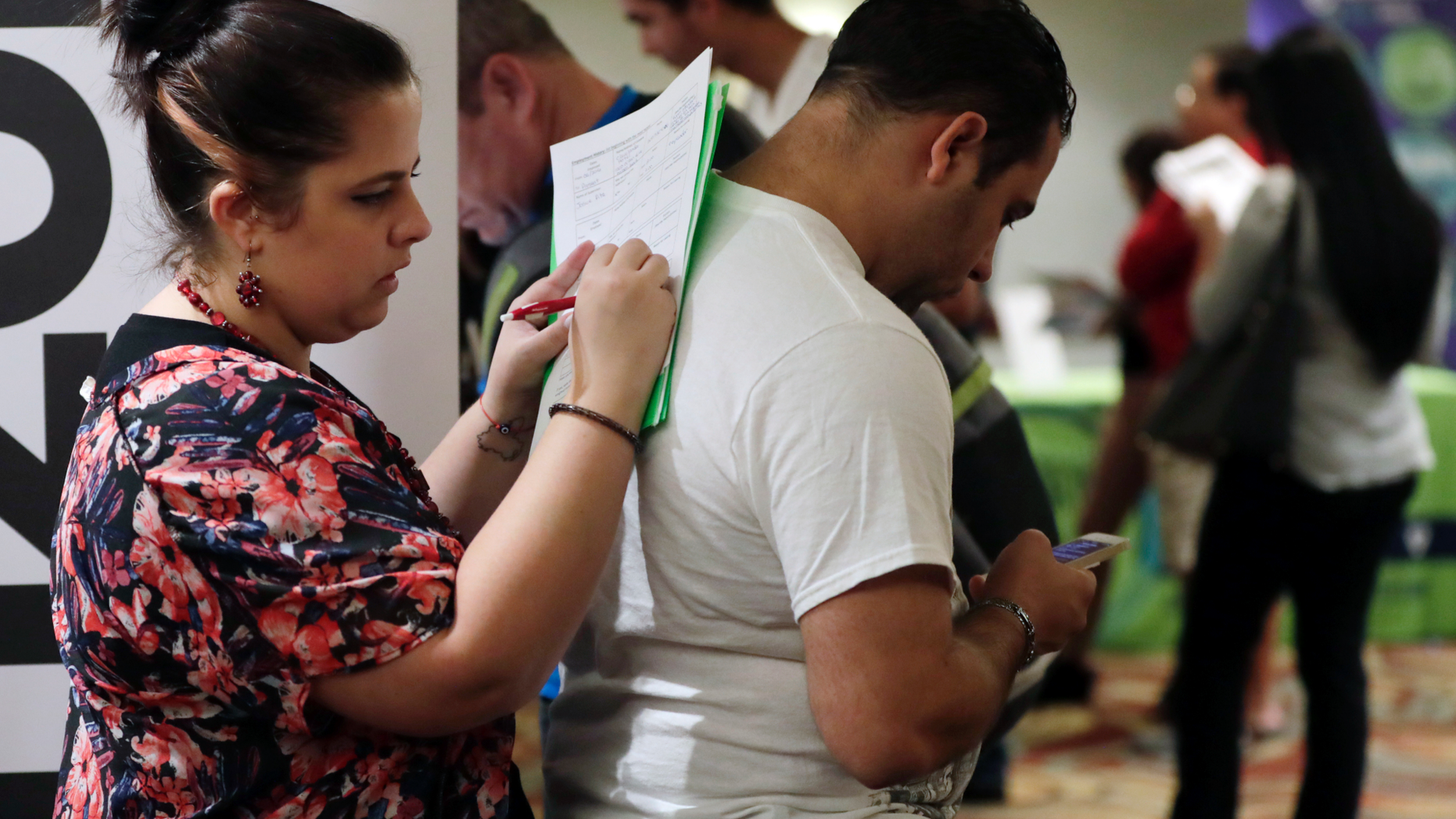 FILE- In this Jan. 30, 2018, file photo, Loredana Gonzalez, of Doral, Fla., fills out a job application at a JobNewsUSA job fair in Miami Lakes, Fla. On Friday, Nov. 2, the U.S. government issues the October jobs report. (AP Photo/Lynne Sladky, File)