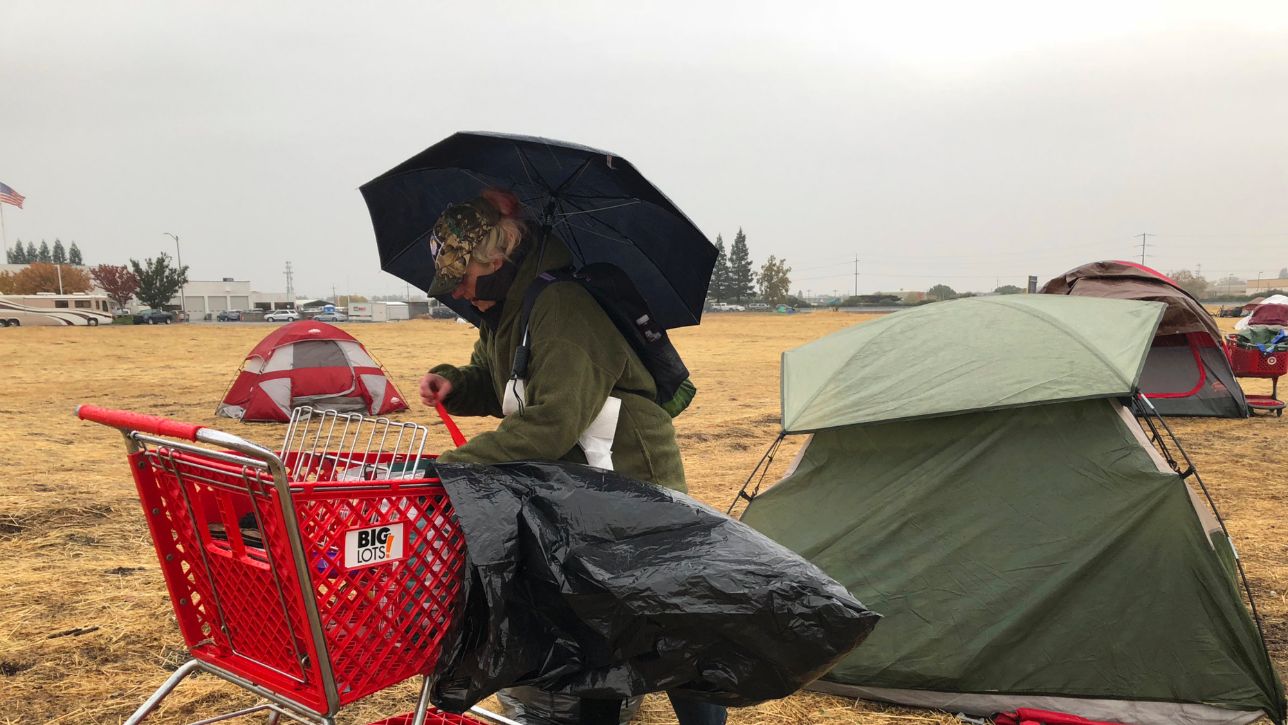 Amy Sheppard packs up items outside her tent in a Walmart parking lot in Chico, Calif., that's been a makeshift campground for people displaced by wildfire, Wednesday morning, Nov. 21, 2018. Sheppard lost her home in Magalia to the Camp fire. She was staying in the tent for four days with her sister and 1-year-old niece. They are moving to a motel because of rain that began Wednesday. (AP Photo/Kathleen Ronayne)