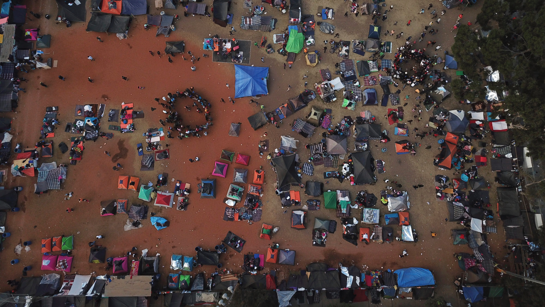 Central American migrants gather in an area designated for them to set up their tents in Tijuana, Mexico, Wednesday, Nov. 21, 2018. Migrants camped in Tijuana after traveling in a caravan to reach the U.S are weighing their options after a U.S. court blocked President Donald Trump's asylum ban for illegal border crossers. (AP Photo/Rodrigo Abd)