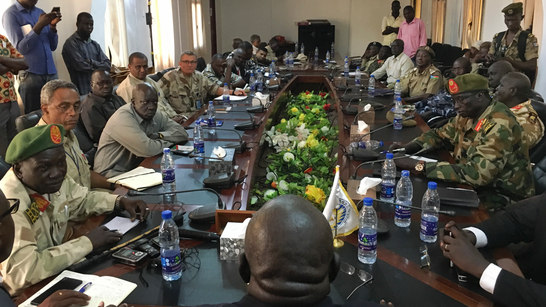In this photo taken Thursday, Nov. 22, 2018, a South Sudan armed opposition commander Ashab Khamis, far-left, and a government army Gen. Keer Kiir Keer, far-right, attend high level talks where both sides exchanged accusations of violating the peace agreement, in Wau, South Sudan. The Associated Press witnessed the first meeting between the Wau region leaders of South Sudan's army and armed opposition since a groundbreaking peace deal, and the country's peace rests on whether the opposing sides can put a vicious past behind. (AP Photo/Sam Mednick)
