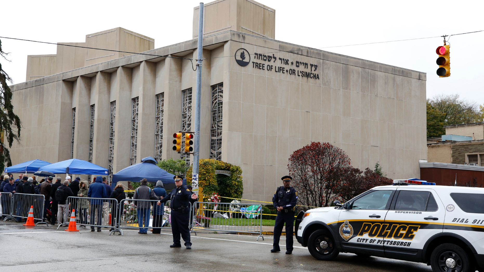 Pittsburgh Police direct traffic as their vehicles close the street adjacent to the Tree of Life Synagogue on Saturday Nov. 3 2018 as a curbside Shabbat morning service is held on the street corner in the Squirrel Hill neighborhood of Pittsburgh. The