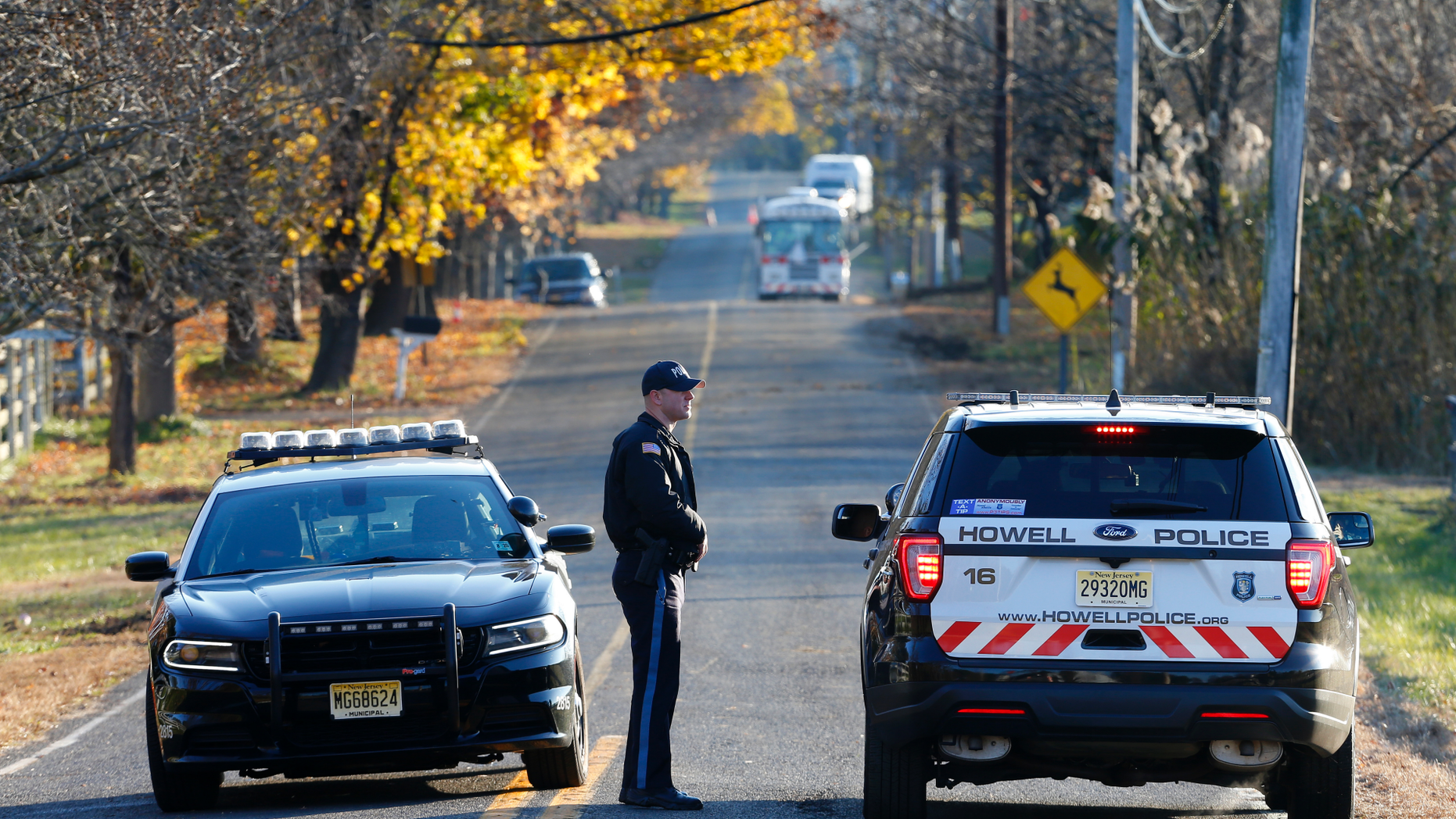 Colts Neck and Howell police officers block the road Wednesday, Nov. 21, 2018, in Colts Neck, N.J., leading to the scene of a fatal fire that killed two children and two adults. Authorities say two adults and two children were found dead the day before at the scene of a burning mansion near the New Jersey shore.  (AP Photo/Noah K. Murray)
