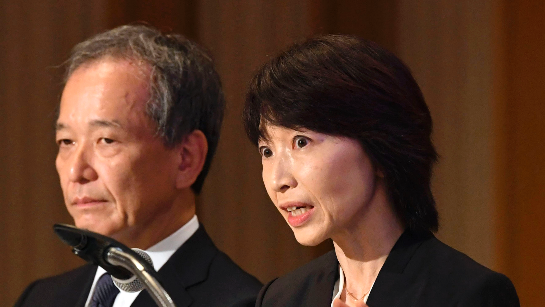 Tokyo Medical University President Yukiko Hayashi, right, speaks during a press conference in Tokyo, Wednesday, Nov. 7, 2018.  The Japanese medical university that has acknowledged systematically discriminating against female applicants has announced plans to accept more than 60 who had been unfairly rejected in the past two years.  The discriminatory policy at Tokyo Medical University surfaced earlier this year, triggering national outrage. The school acknowledged in August that it has been slashing female applicants' entrance exam scores for years to keep the female student population low, saying women tend to quit as doctors after starting families.(Kyodo News via AP)