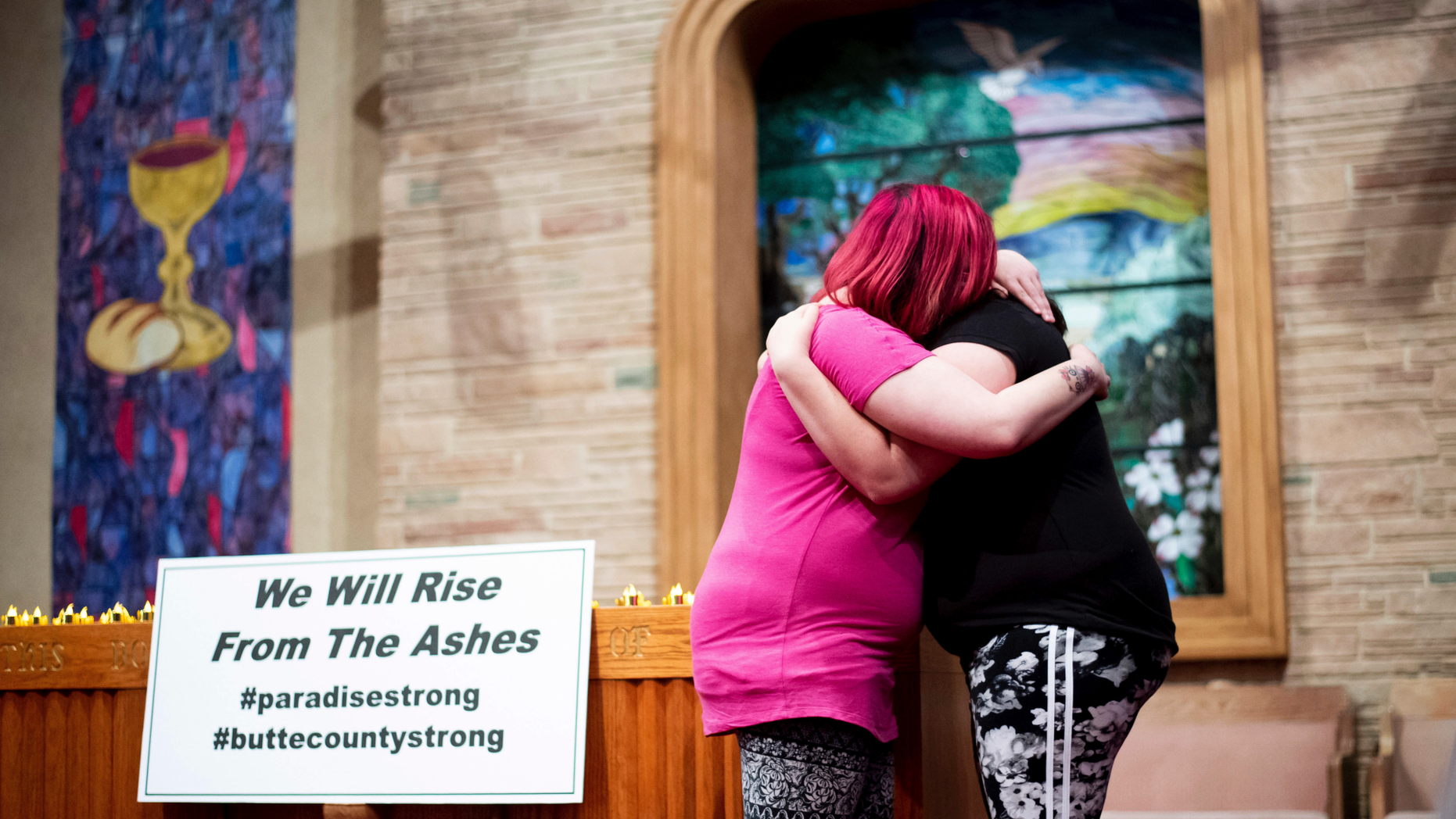 Sisters Alli Benefield, left, and Kassy Parish embrace during a vigil for the lives and community lost to the Camp Fire on Sunday, Nov. 18, 2018, at the First Christian Church of Chico in Chico, Calif. More than 50 people gathered at the memorial for the victims. People hugged and shed tears as Pastor Jesse Kearns recited a prayer for first responders. (AP Photo/Noah Berger, Pool)