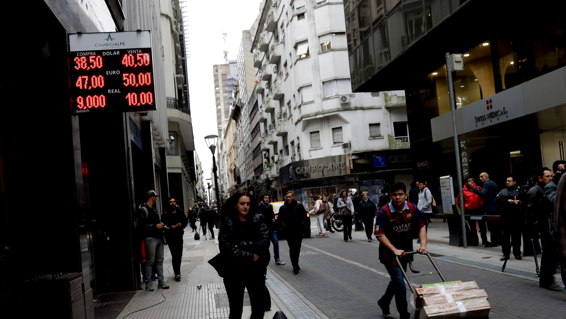 FILE - In this Aug. 30, 2018 file photo, people walk past an exchange house in Buenos Aires, Argentina. Argentina had hoped to show off its newly market-friendly economy to the world when the G-20 group of the world's top economies begins its first South American summit in late November, but instead it's looking for help to avoid an all-out crisis. (AP Photo/Natacha Pisarenko, File)