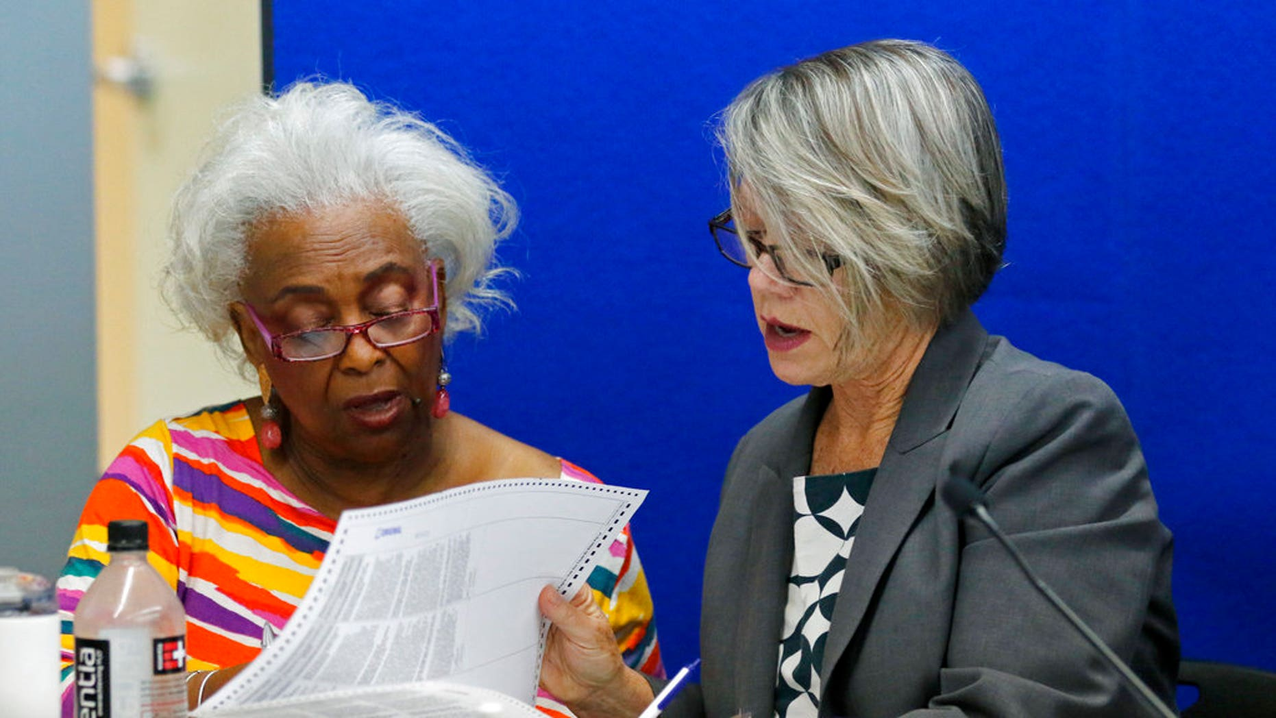 Dr. Brenda Snipes, left, Broward County Supervisor of Elections, looks at a ballot with Betsy Benson, canvasing board chair during a canvasing board meeting on the bitter and tight U.S. Senate race between Republican Gov. Rick Scott and incumbent Democrat Bill Nelson; and in the governor's race between former Republican U.S. Rep. Ron DeSantis and the Democratic mayor of Tallahassee, Andrew Gillum. (AP Photo/Joe Skipper)