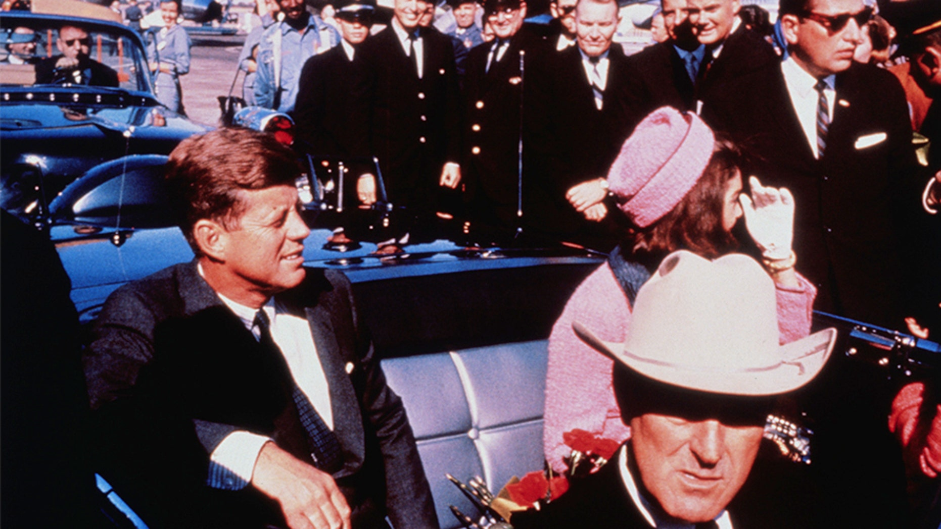 Texas Governor John Connally adjusts his tie (foreground) as President and Mrs. Kennedy, in a pink outfit, settled in rear seats, prepared for motorcade into the city from the airport, Nov. 22. After a few speaking stops, the President was assassinated in the same car.