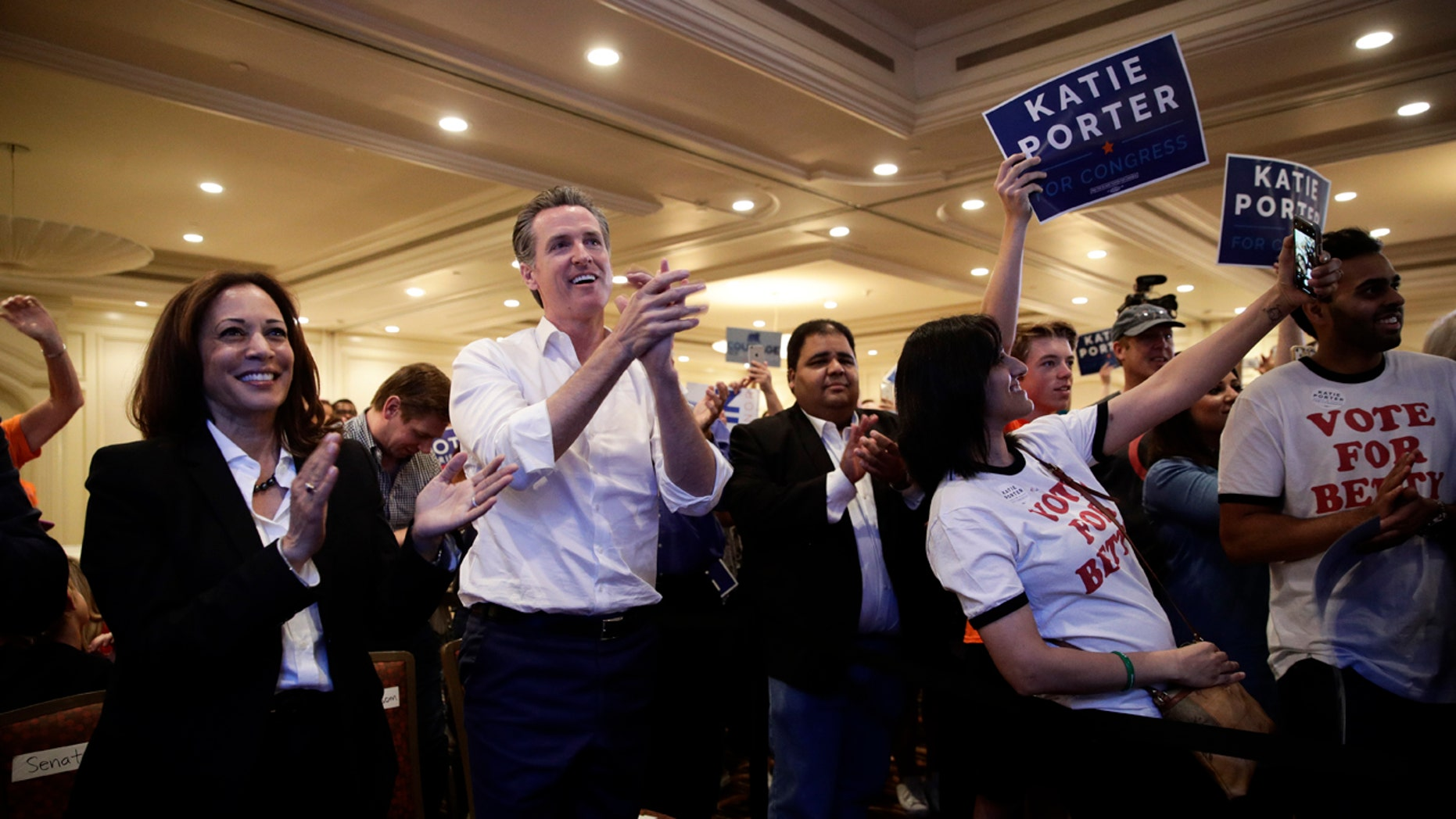 Sen. Kamala Harris, D-Calif., left, and California gubernatorial Democratic candidate Gavin Newsom applaud as they listen to Katie Porter, a congressional candidate for California's 45th District, during a campaign rally Saturday, Nov. 3, 2018, in Irvine, Calif. The fight for control of the U.S. House is attracting big names to historically Republican Orange County, California. (AP Photo/Jae C. Hong)