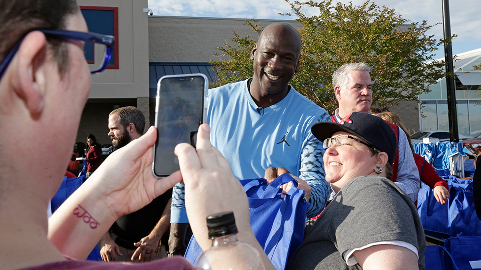 Charlotte Hornets owner Michael Jordan poses for a photo while greeting people and handing out food for Thanksgiving to members of the community in Wilmington, N.C., Tuesday. (AP Photo/Gerry Broome)