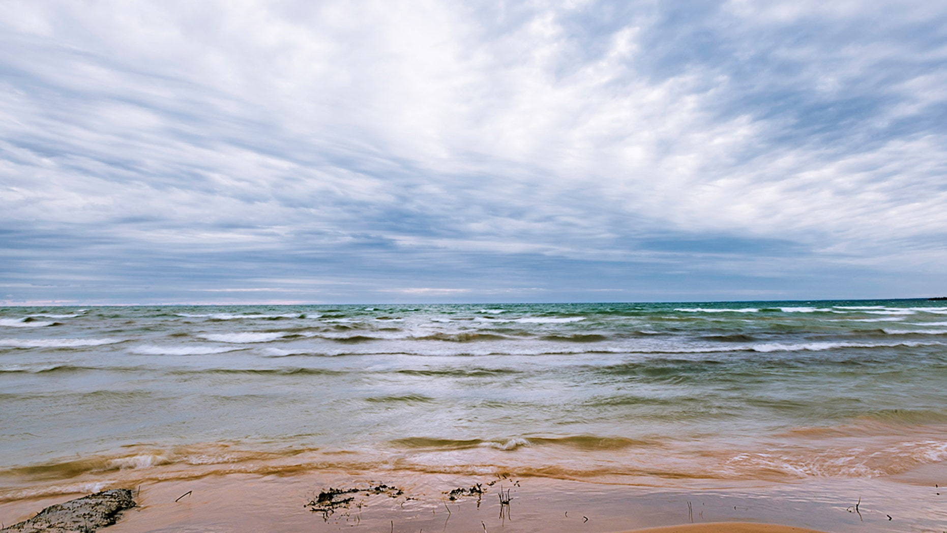 A man died and a woman remains missing Monday after they encountered hazardous conditions while swimming in Lake Michigan, officials said.