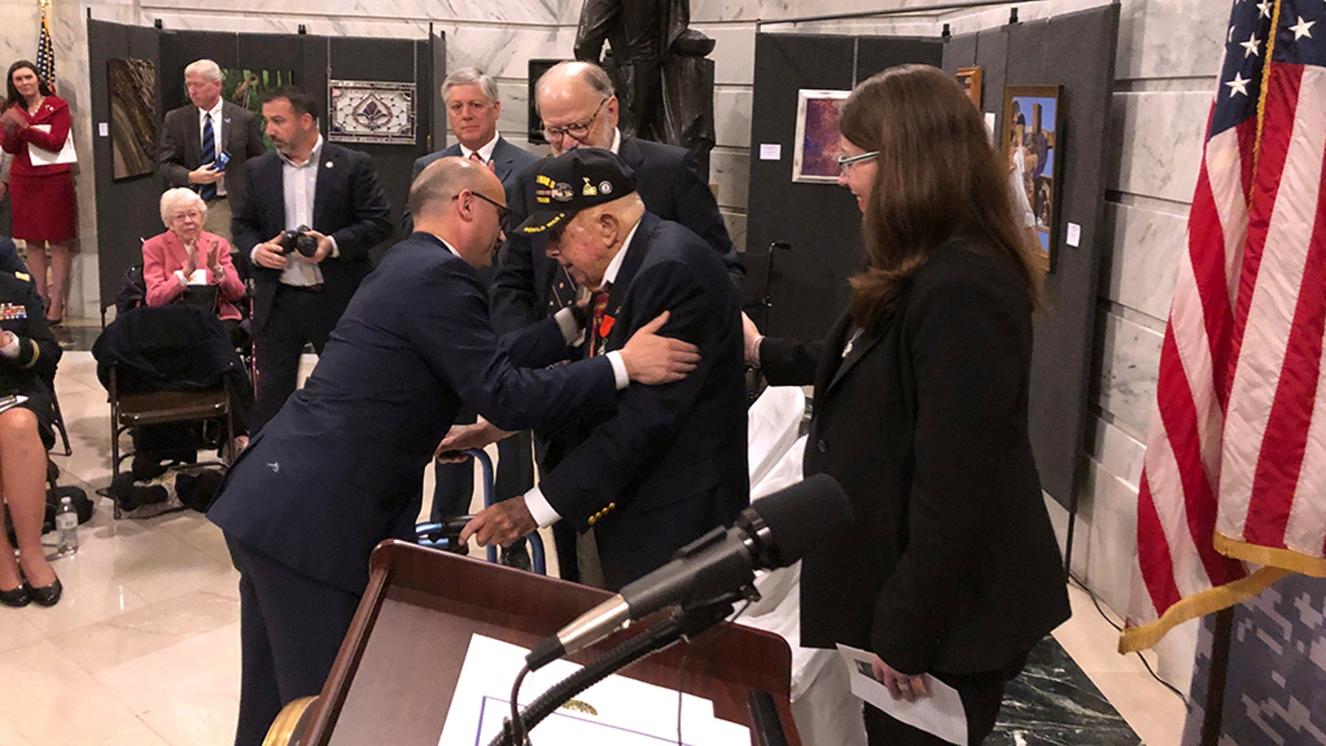 French Consul General Guillaume Lacroix, left, embraces retires Lt. Col. William Pollard after awarding him the French Legion of Honor on Monday, Nov. 19, 2018, in Frankfort, Kentucky. Pollard is a 100-year-old World War II veteran who lives in Kentucky. He was part of the Allied invasion of France in 1944. (AP Photo/Adam Beam)