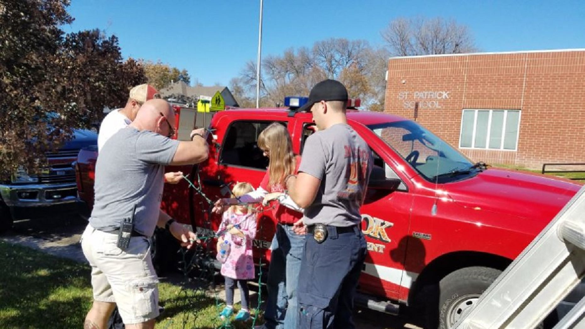 The McCook Fire Department gathered to help the family of Raleigh Haas put up Raleigh's Christmas lights.