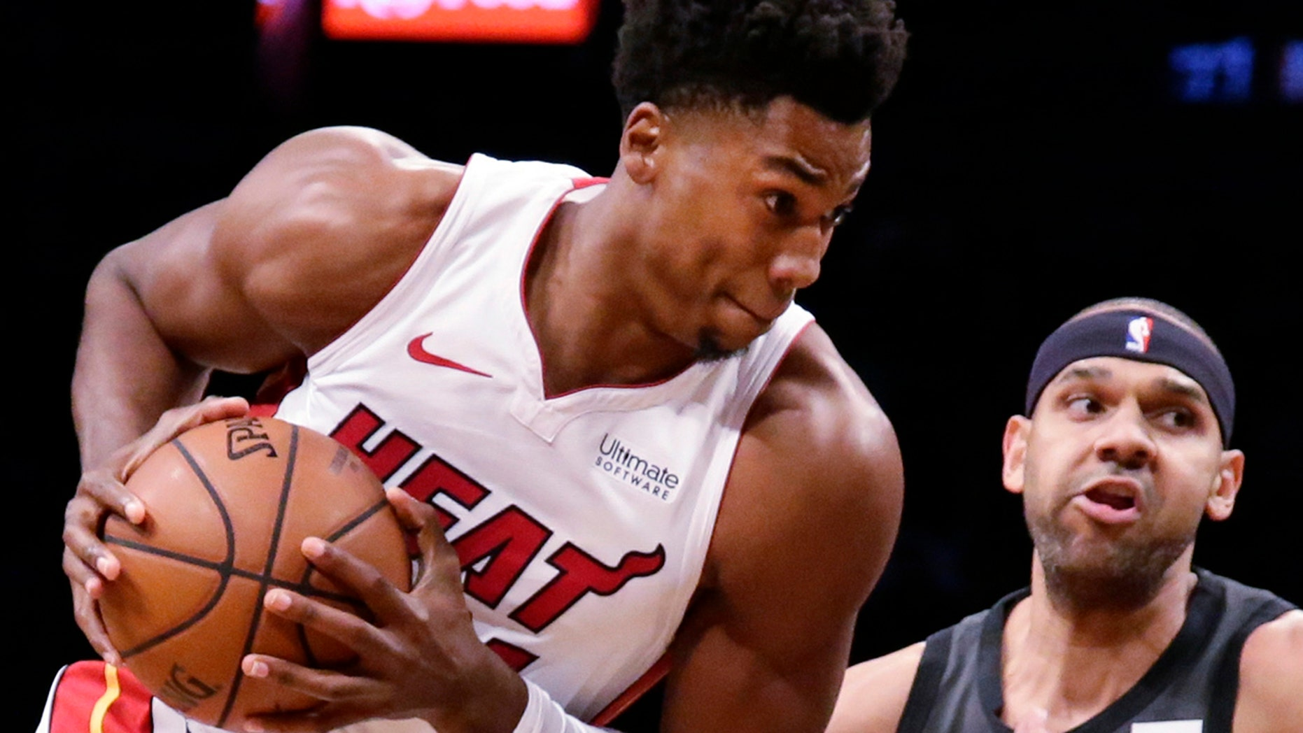 Miami Heat's Hassan Whiteside (21) drives past Brooklyn Nets' Jared Dudley (6) during the first half of an NBA basketball game Wednesday, Nov. 14, 2018, in New York.