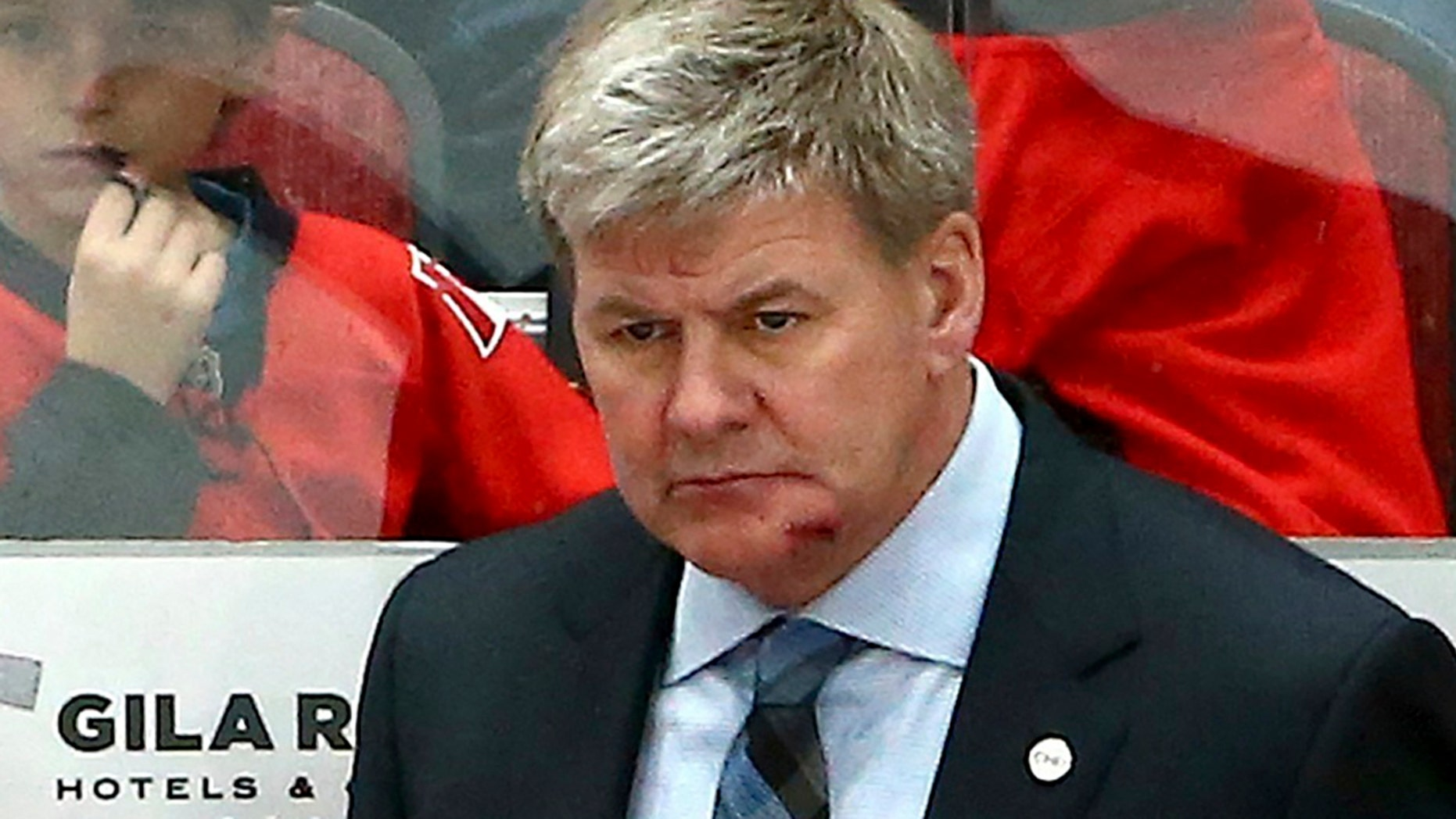 Calgary Flames head coach Bill Peters, top, returns to the bench with a gash on his chin after being hit with the puck earlier in the hockey game.