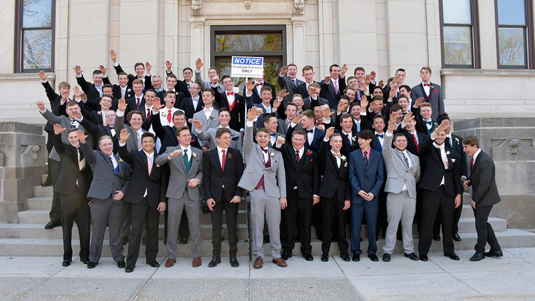 In this May 2018 photo provided by Peter Gust, a group of Wisconsin high school boys stand on the steps outside the Sauk County Courthouse in Baraboo, Wis. The image has drawn widespread condemnation because of the appearance that some of the students are giving a Nazi salute. Gust, who has a son in the photo, denies there was an intent to offend anyone and says they are waving goodbye to their parents before they head to prom. (Peter Gust via AP)