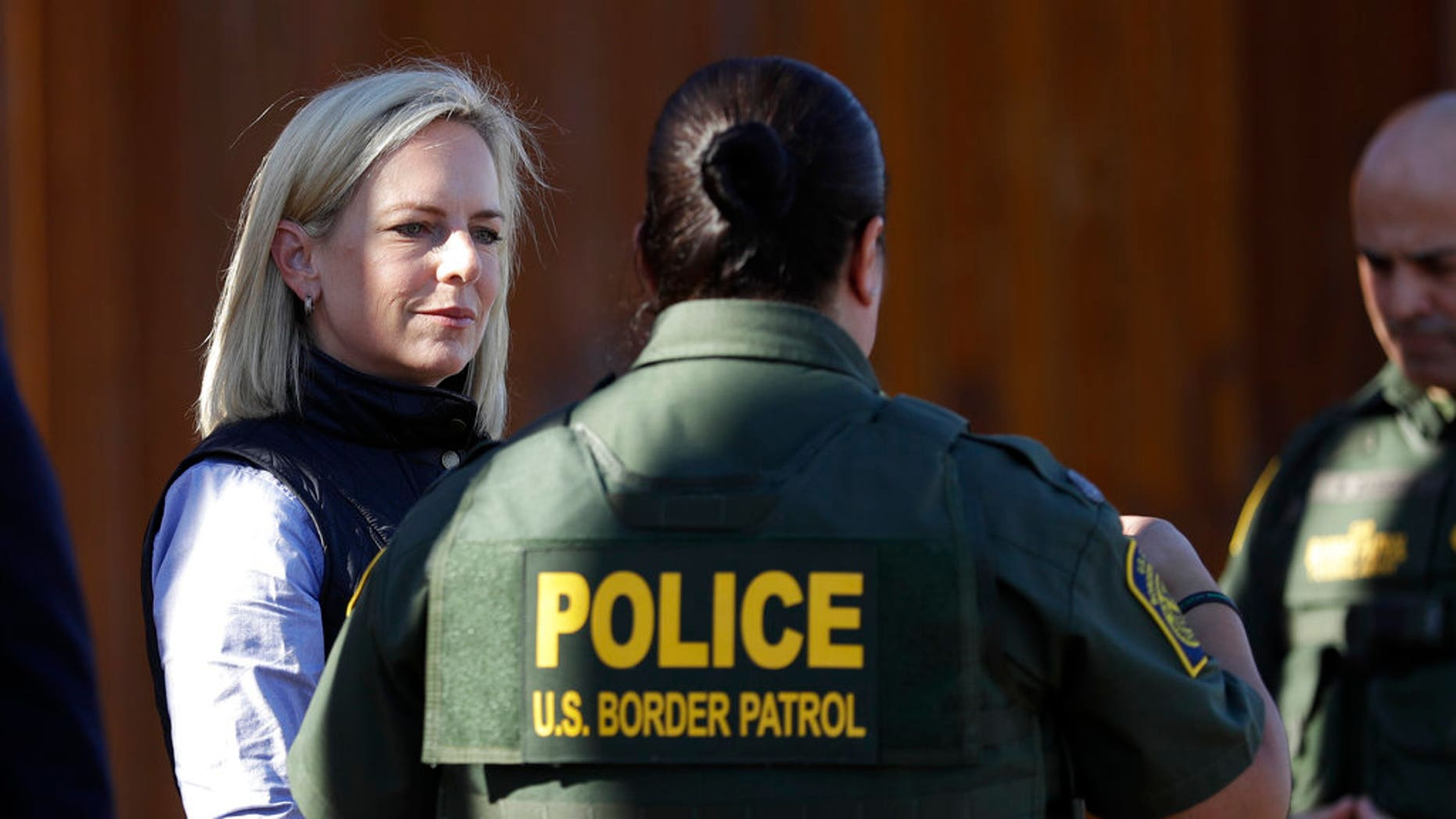U.S. Department of Homeland Security Secretary Kirstjen Nielsen, left, speaks with Border Patrol agents near a newly fortified border wall structure in Calexico, Calif. (AP Photo/Gregory Bull)