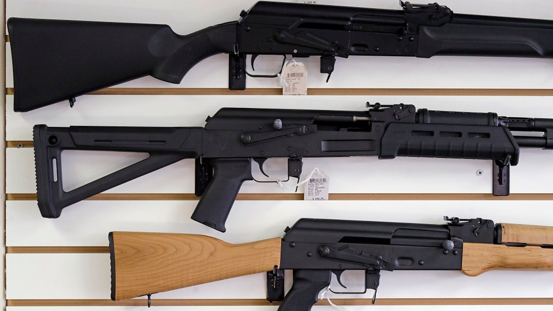 FILE - Semi-automatic rifles are displayed on a wall during a gun shop.