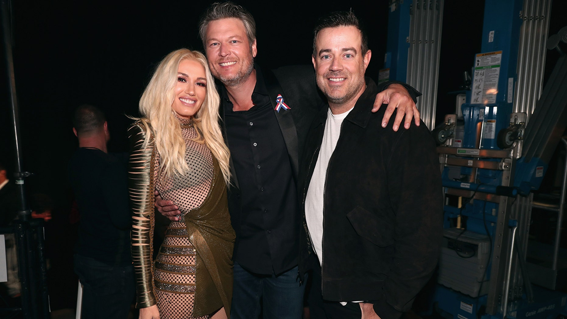 Pictured: (l-r) Recording artists-TV personalities Gwen Stefani and Blake Shelton and TV personality Carson Daly pose during the 2018 E! People's Choice Awards held at the Barker Hangar on November 11, 2018.