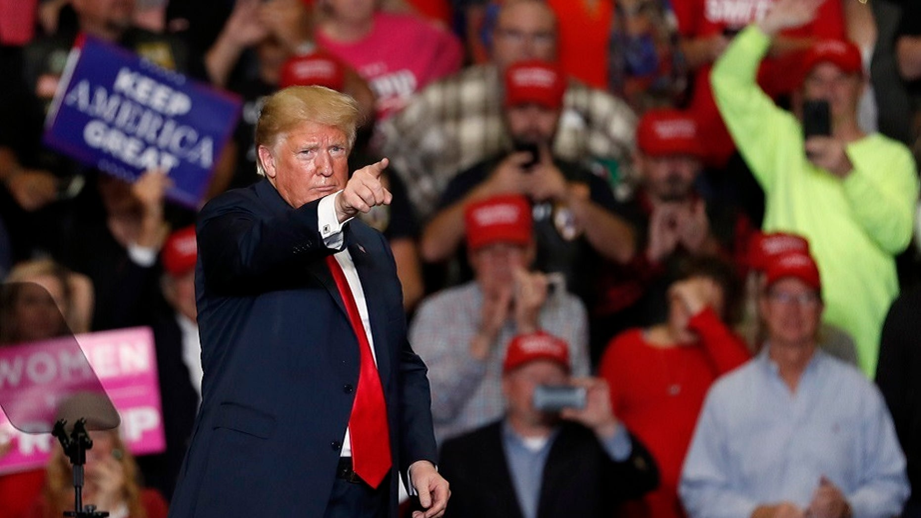 President Donald Trump points to the crowd as he leaves the stage at the end of a campaign rally Monday.