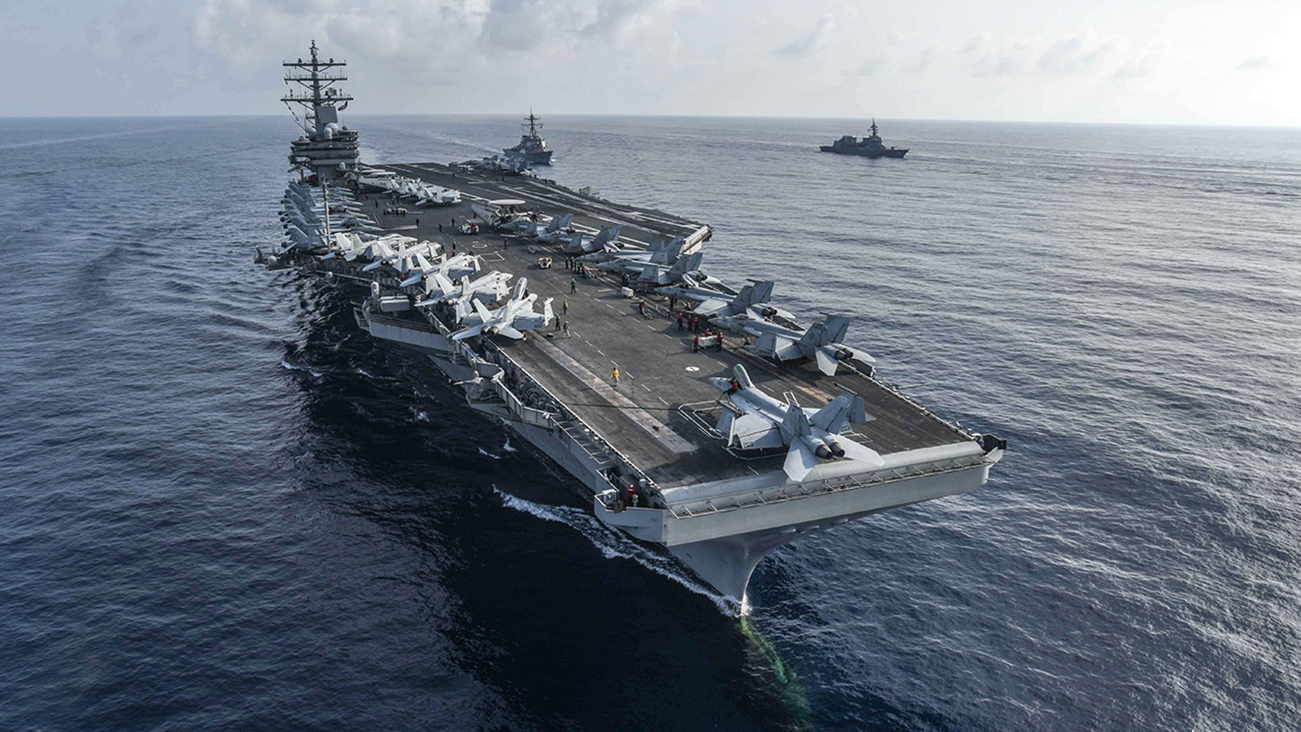 The aircraft carrier USS Ronald Reagan and the guided-missile destroyer USS Milius, center, conduct a photo exercise with Japan Maritime Self-Defense Force ships. (U.S. Navy)