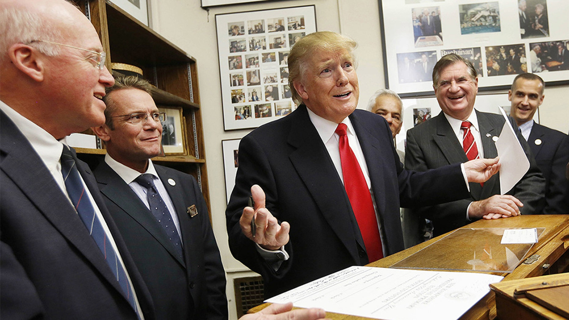 In this Nov. 4, 2015, file photo, New Hampshire Secretary of State Bill Gardner, left, watches as then-Republican presidential candidate Donald Trump fills out his filing papers to be on the primary ballot at the Secretary of State's office in Concord, N.H. (AP Photo/Jim Cole, File)