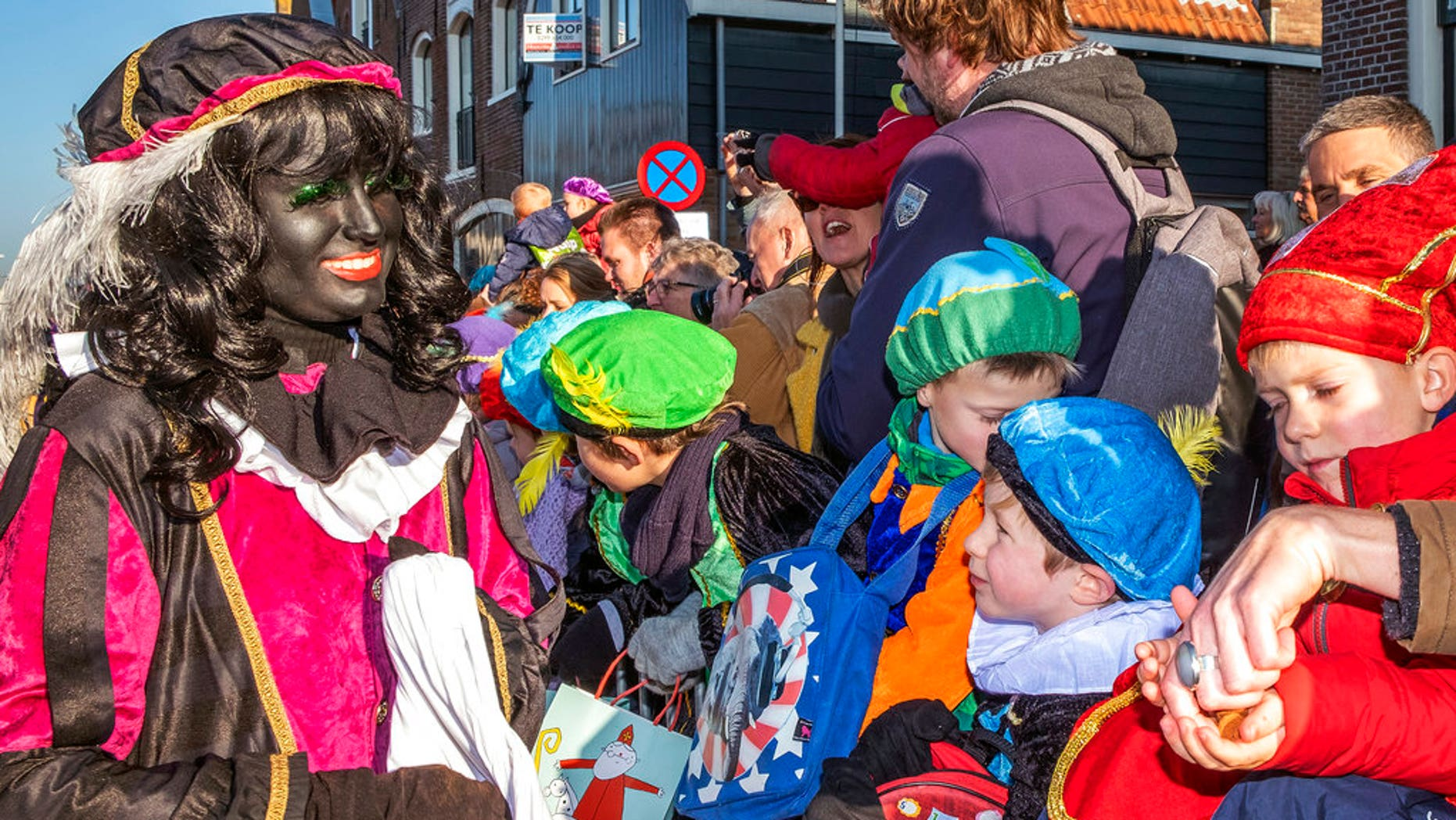 A Black Pete interacts with children during the arrival of Sinterklaas in Monnickendam, Netherlands, Saturday, Nov. 17, 2018. White people often daub their faces with black paint when they dress up to play the character. Opponents say such depictions of Black Pete promote racist stereotypes. Supporters defend the sidekick of Sinterklaas, the white-bearded, red-robed Dutch version of St. Nicholas, as a traditional children's character. (AP Photo/Patrick Post)
