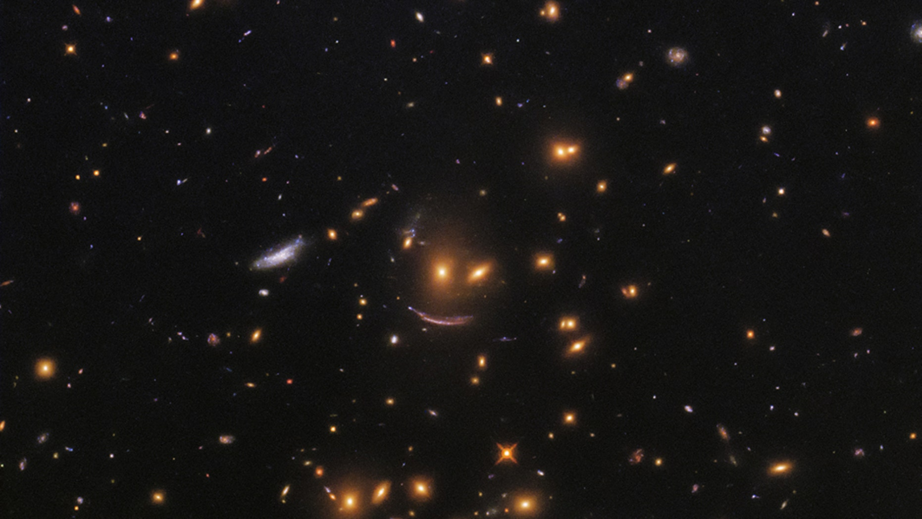"""NASArecently shared a photo taken by the Hubble Space Telescope that shows a formation of galaxies forming what looks like a smiley face.<br data-cke-eol=""""1"""">"""