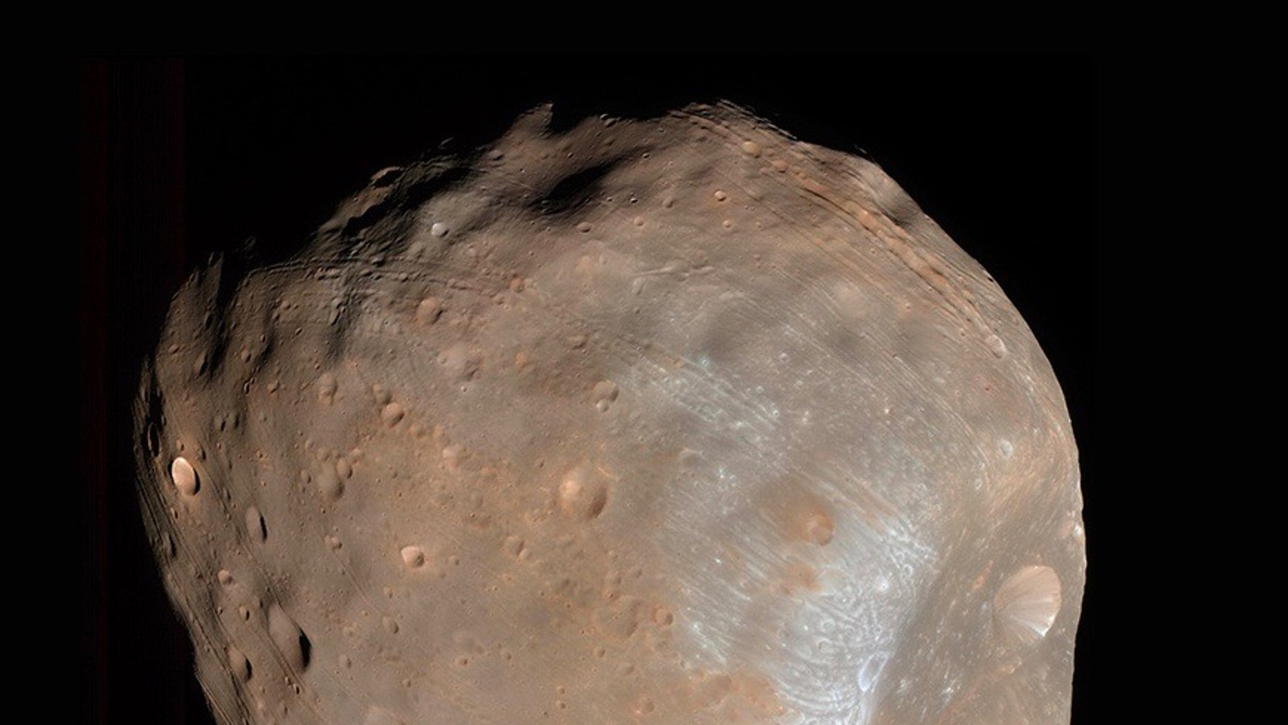 The strange grooves on the surface of the tiny Mars moon Phobos (seen here by NASA's Mars Reconnaissance Orbiter) were made by rolling boulders knocked loose by a giant impact, a new study suggests.