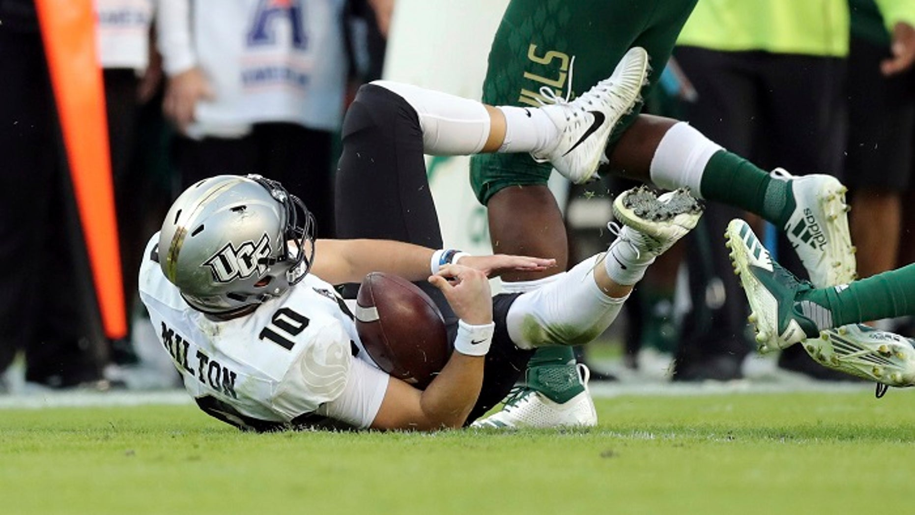 UCF quarterback McKenzie Milton goes down with an apparent knee injury after being tackled in a game against South Florida on Friday, Nov. 23, 2018.