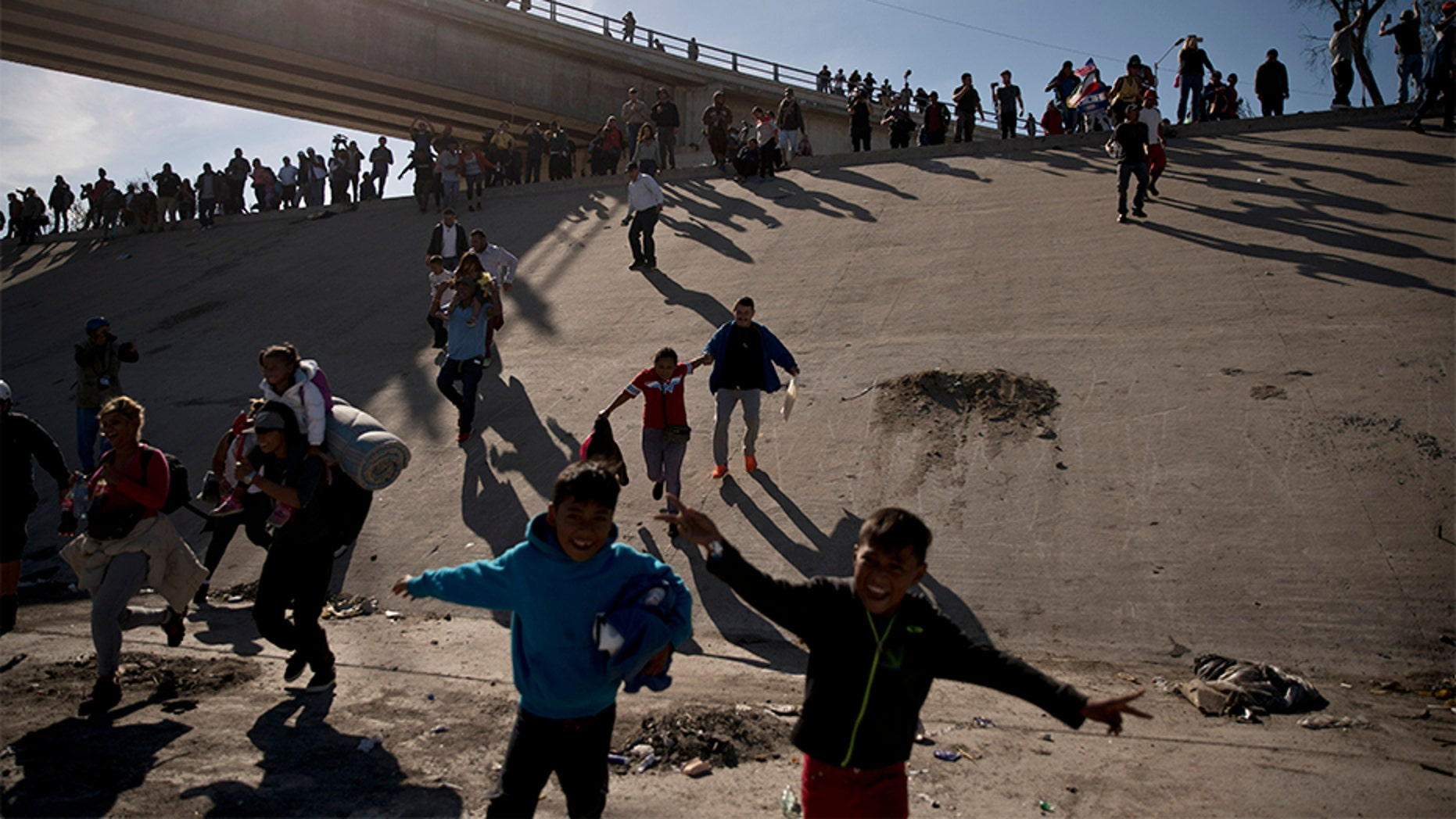 Migrants cross the river at the Mexico-U.S. border after pushing past a line of Mexican police at the Chaparral crossing in Tijuana, Mexico, on Sunday.