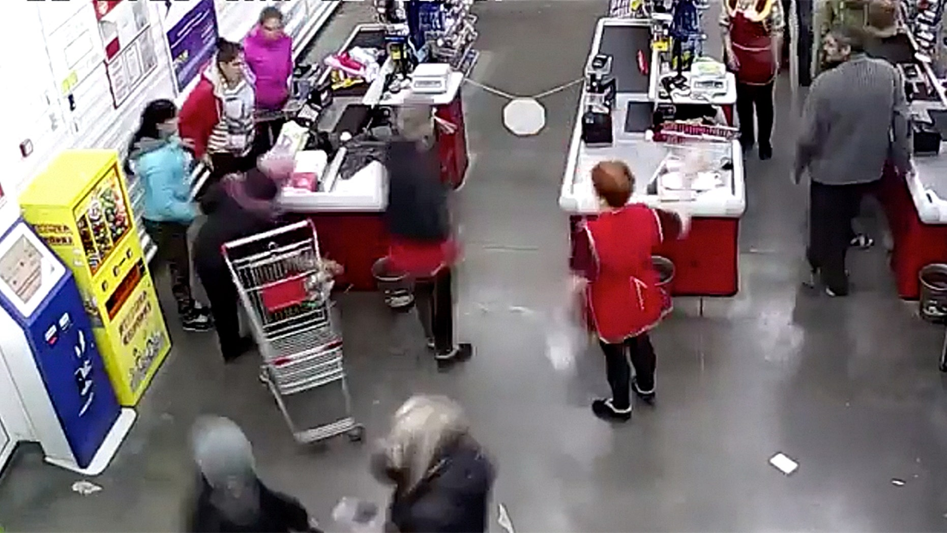 The mother, pictured left at the checkout counter in a red coat, told her cashier that she couldn't wait any longer and that her baby was coming any minute.
