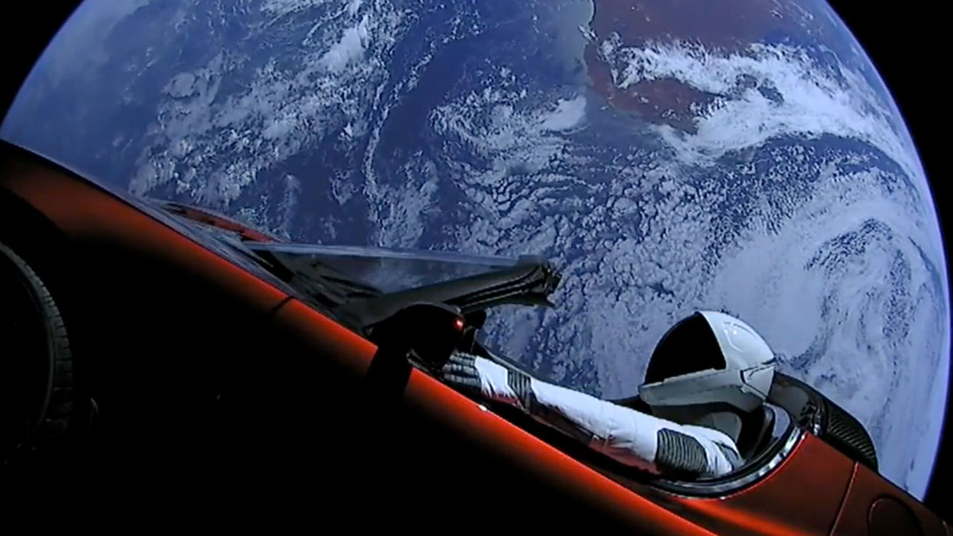 SpaceX's Starman mannequin is seen inside Elon Musk's red Tesla Roadster with Earth in the background, shortly after launch on Feb. 6, 2018. As of Nov. 2, the duo were beyond the orbit of Mars.