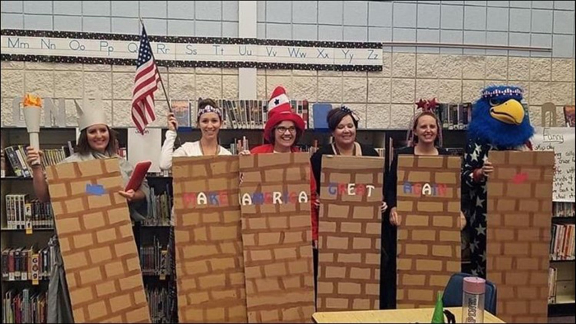 A school district is investigating after photos showed school employees dressed as a border wall.