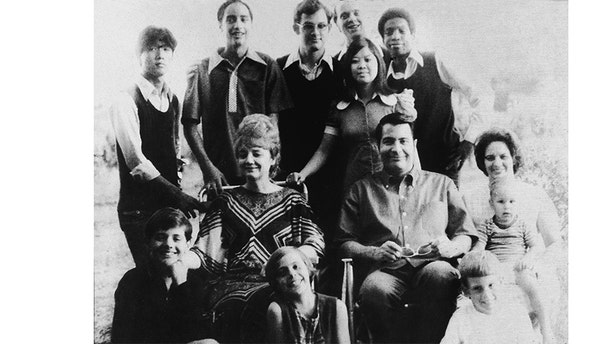 Portrait of Jim Jones and his wife, Marceline Jones seated in front of their adopted children and next to his sister-in-law (right) with her three children, California, 1976.
