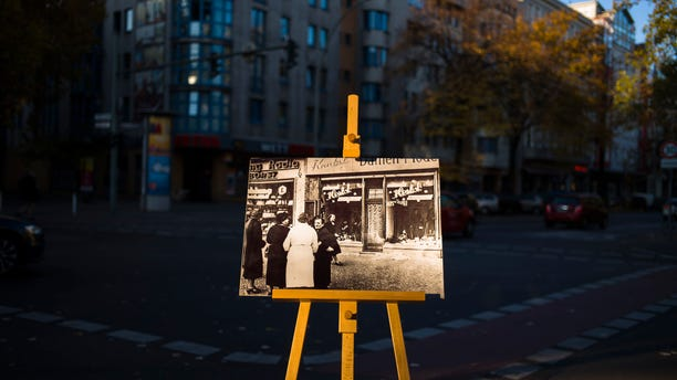 A Nov. 10, 1938 photo from the AP Archive, showing by Nazis destroyed shops at the Potsdamer Strasse street, is placed at the same location 80 years later in Berlin, Germany. (AP Photo/Markus Schreiber)