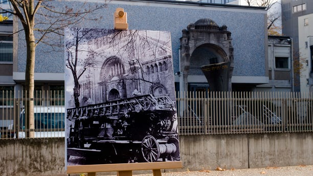 A Nov. 10, 1938 photo from the AP Archive, showing a fire engine outside the Jewish synagogue on Fasanenstrasse that was burned by Nazis during Kristallnacht, is placed at the same location 80 years later in Berlin. (AP Photo/Markus Schreiber)