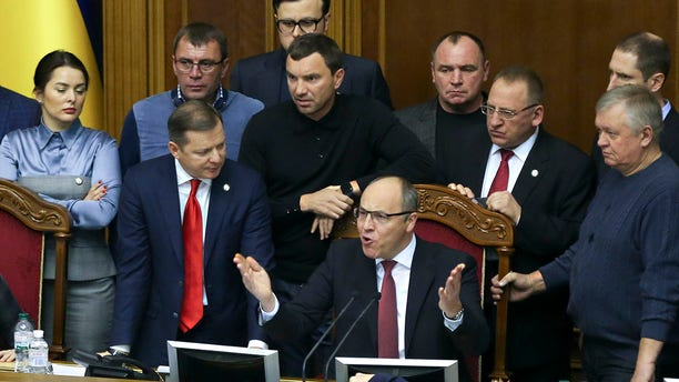 Ukrainian lawmakers listen to parliament speaker Andriy Parubiy, center, during a parliament session in Kiev, Ukraine, Monday, Nov. 26, 2018. Ukrainian President Petro Poroshenko has signed a bill to impose martial law in the country in the wake of Russia's seizure of three ships and their crews. The Supreme Rada is due to vote on the issue later Monday for it to go into force. (AP Photo/Efrem Lukatsky)