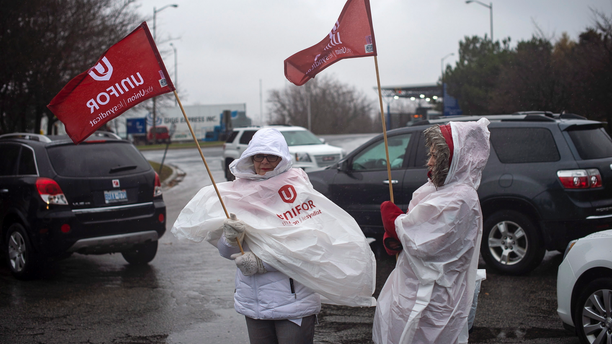 Members of Unifor, the union representing the workers of Oshawa's General Motors assembly plant, stand near the entrance to the plant in Oshawa, Ontario, Monday, Nov. 26, 2018. General Motors will lay off thousands of factory and white-collar workers in North America and put five plants up for possible closure as it restructures to cut costs and focus more on autonomous and electric vehicles. General Motors is closing the Oshawa plant. (Eduardo Lima/The Canadian Press via AP)