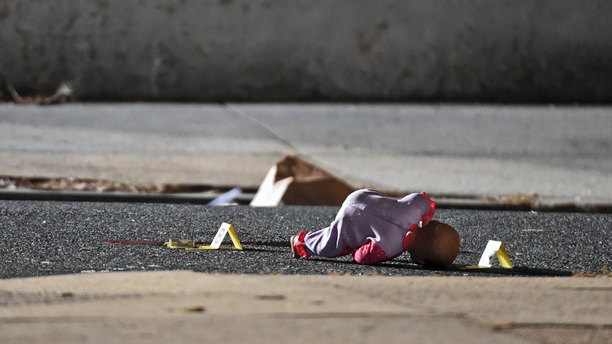In this Monday, Nov. 19, 2018, photo, a child's doll lays next to police shooting evidence tags, as Baltimore City Police officers investigate the scene of a shooting at the 1000 block of McKean Avenue in Baltimore, where authorities say a 5-year-old girl was shot and wounded. The child l was to the hospital and immediately taken into surgery. Police were told she was alert and able to talk to doctors (Kenneth K. Lam/The Baltimore Sun via AP)