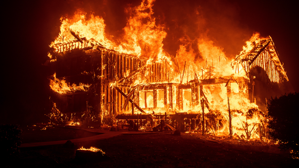 A home burns as the Camp Fire rages through Paradise, Calif., on Thursday, Nov. 8, 2018. Tens of thousands of people fled a fast-moving wildfire Thursday in Northern California, some clutching babies and pets as they abandoned vehicles and struck out on foot ahead of the flames that forced the evacuation of an entire town. (AP Photo/Noah Berger)