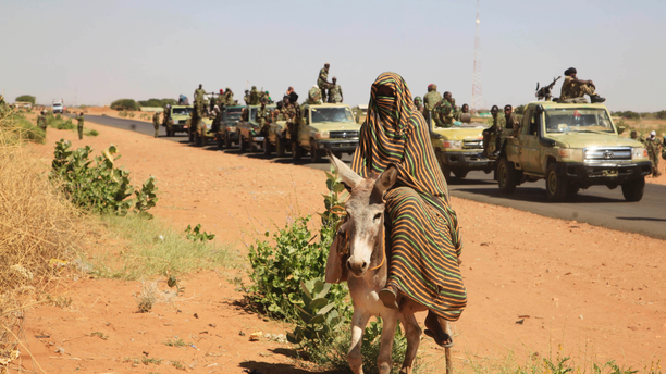 FILE - In this Thursday, Nov. 20, 2014 photo taken on a government organized media tour, a woman rides a donkey past a convoy of government troops in Tabit village in the North Darfur region of Sudan, where allegations surfaced of rape of women by government allied troops. Human Rights Watch is cautioning the United States against lifting its designation of Sudan as a state sponsor of terrorism. The New York-based watchdog said Thursday, Nov. 8, 2018 that Khartoum continues to violate basic human rights, with security forces regularly attacking civilians and opening fire on peaceful protesters.(AP Photo/Abd Raouf, File)