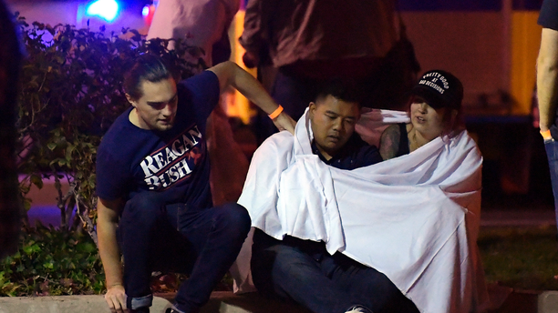 """People comfort each other as they sit near the scene Thursday, Nov. 8, 2018, in Thousand Oaks, Calif. where a gunman opened fire Wednesday inside a country dance bar crowded with hundreds of people on """"college night,"""" wounding 11 people including a deputy who rushed to the scene. Ventura County sheriff's spokesman says gunman is dead inside the bar. (AP Photo/Mark J. Terrill)"""