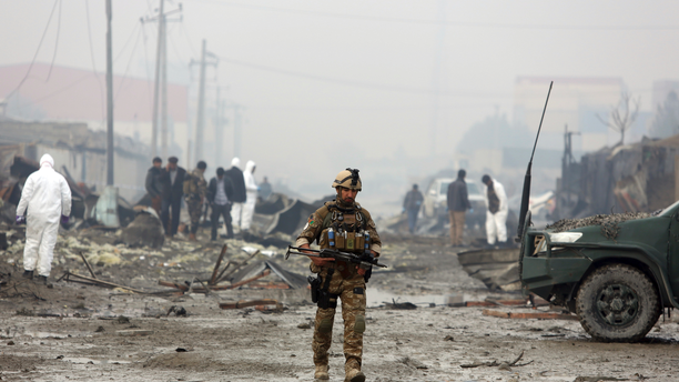 An Afghan security force walks around the site of suicide bomb attack in Kabul, Afghanistan, Thursday, Nov. 29, 2018. Taliban insurgents staged a coordinated attack targeting a security firm in the Afghan capital on Wednesday, killing people and wounding others.