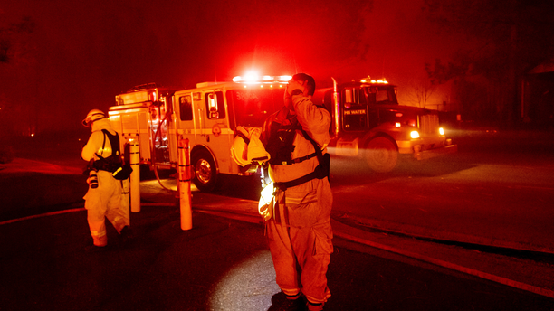 Firefighter Adrien Mahnke pauses while battling the Camp Fire as it tears through Paradise, Calif., on Thursday, Nov. 8, 2018. Tens of thousands of people fled a fast-moving wildfire Thursday in Northern California, some clutching babies and pets as they abandoned vehicles and struck out on foot ahead of the flames that forced the evacuation of an entire town and destroyed hundreds of structures. (AP Photo/Noah Berger)