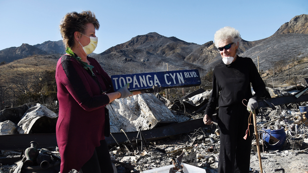 Donna Phillips, left, finds an intact street sign amid the charred possessions of her friend Marsha Maus, right, Sunday, Nov. 11, 2018, after a wildfire tore through the Seminole Springs Mobile Home Park in Agoura Hills, Calif. Maus has been a resident of the neighborhood for 15 years. (AP Photo/Chris Pizzello)