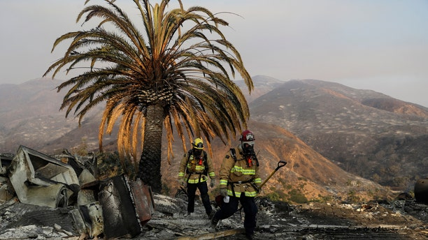 Firefighters Jason Toole, right, and Brent McGill with the Santa Barbara Fire Dept. walk among the ashes of a wildfire-ravaged home after turning off an open gas line on the property Saturday, Nov. 10, 2018, in Malibu, Calif.